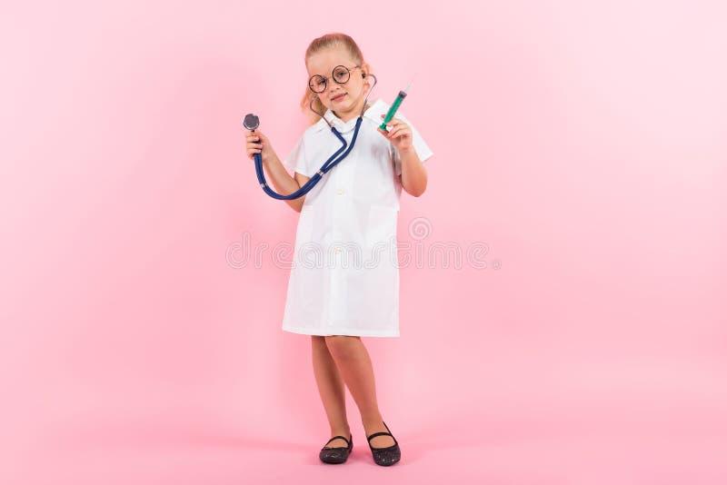 Маленькая девочка в костюме доктора с впрыской стоковые фото