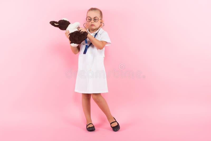 Маленькая девочка в костюме доктора с игрушкой стоковое изображение rf