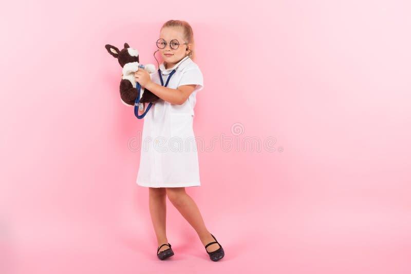 Маленькая девочка в костюме доктора с игрушкой стоковые изображения