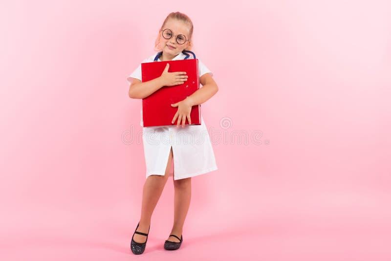 Маленькая девочка в костюме доктора с папкой стоковое изображение rf