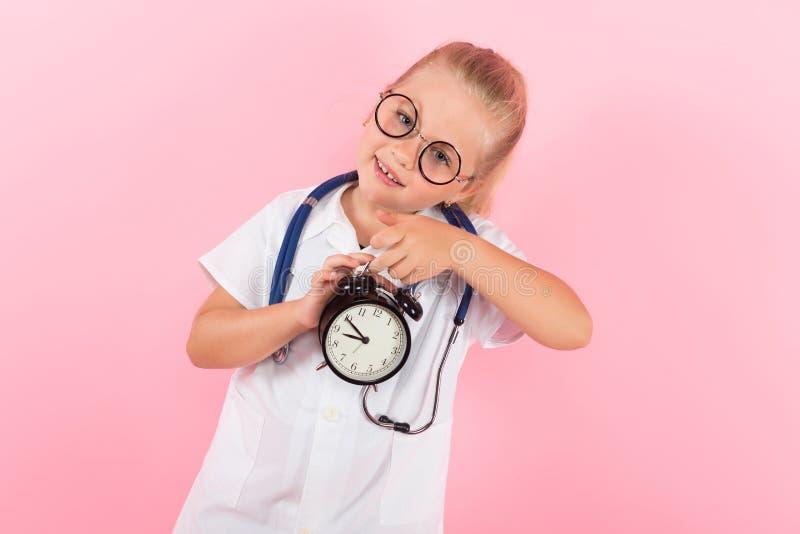 Маленькая девочка в костюме доктора с часами стоковые изображения