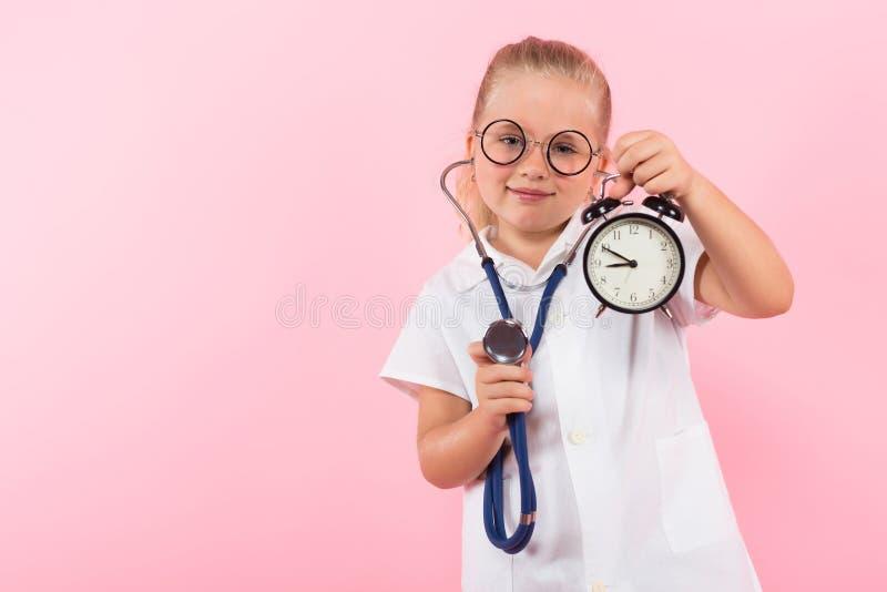 Маленькая девочка в костюме доктора с часами стоковые фотографии rf