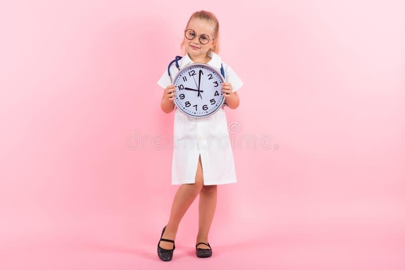 Маленькая девочка в костюме доктора с часами стоковое изображение rf