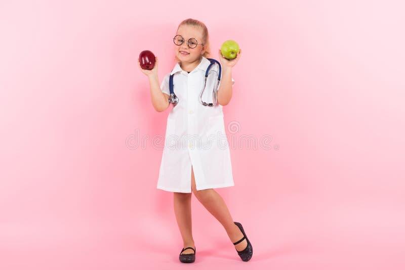 Маленькая девочка в костюме доктора с яблоками стоковая фотография