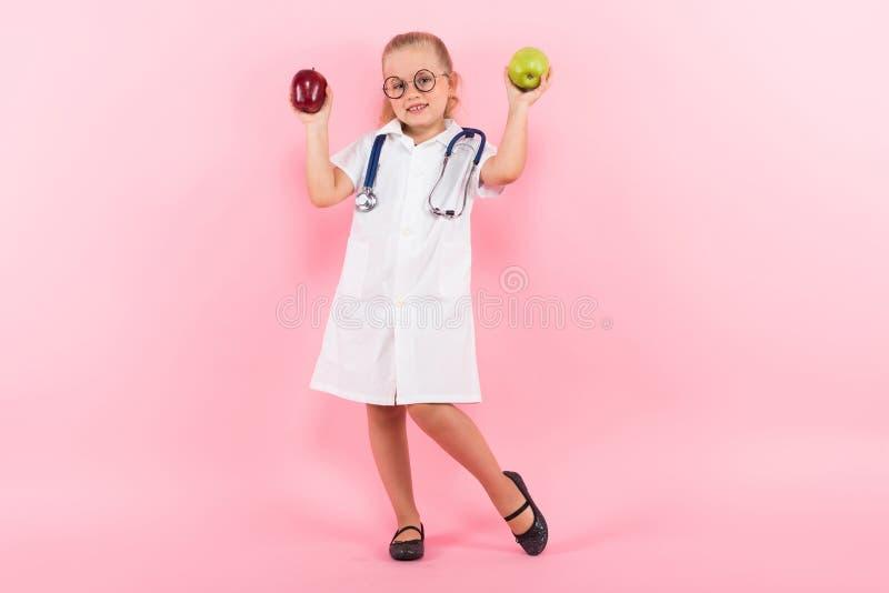 Маленькая девочка в костюме доктора с яблоками стоковое изображение rf