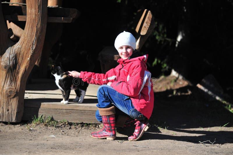 Маленькая девочка в красной куртке штрихуя кота стоковые фото