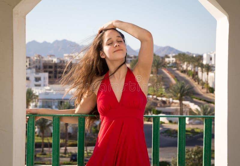 Маленькая девочка в красном платье наслаждаясь на балконе гостиницы стоковые изображения rf