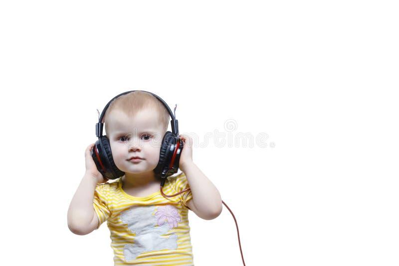Маленькая девочка в наушниках слушая музыку стоковое фото rf