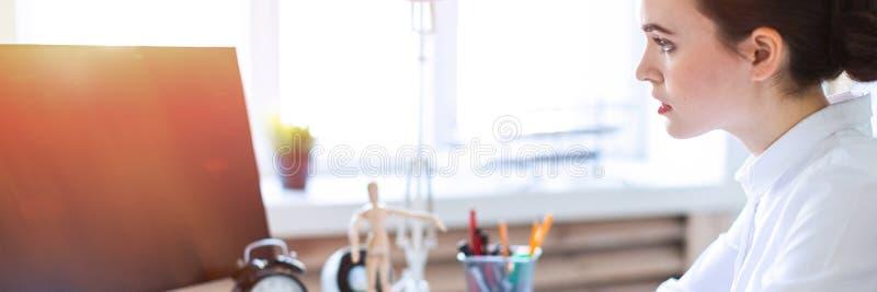 Маленькая девочка в офисе сидит на таблице, работает с компьютером, калькулятором, документами и владениями отметка и ручка внутр стоковые изображения