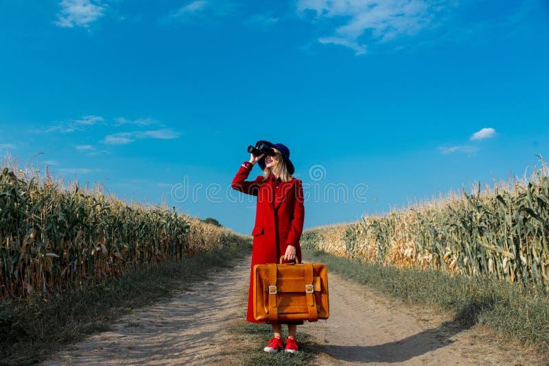 Маленькая девочка в пальто с чемоданом и биноклями стоковое изображение