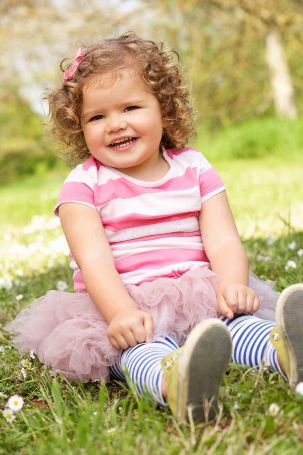 Маленькая девочка в платье лета сидя в поле стоковая фотография rf