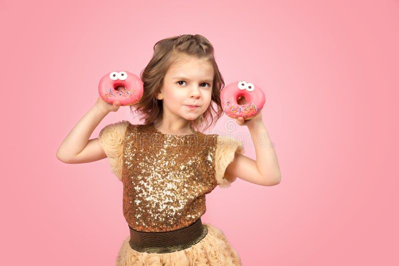 Маленькая девочка в платье с donuts стоковое фото