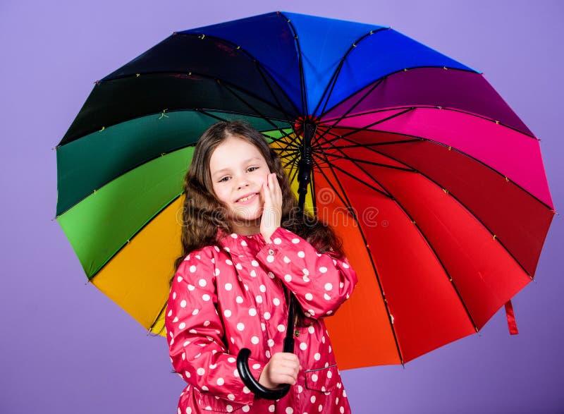 Маленькая девочка в плаще счастливая маленькая девочка с красочным зонтиком предохранение от дождя Радуга мода осени o стоковые изображения rf