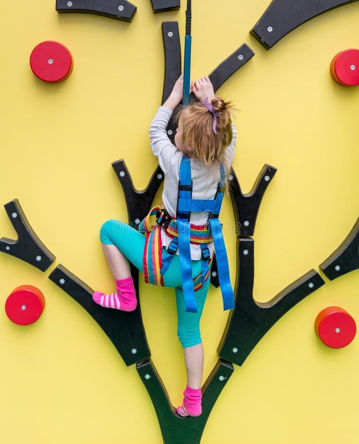 Маленькая девочка в поездах страхования на взбираясь стене стоковые изображения