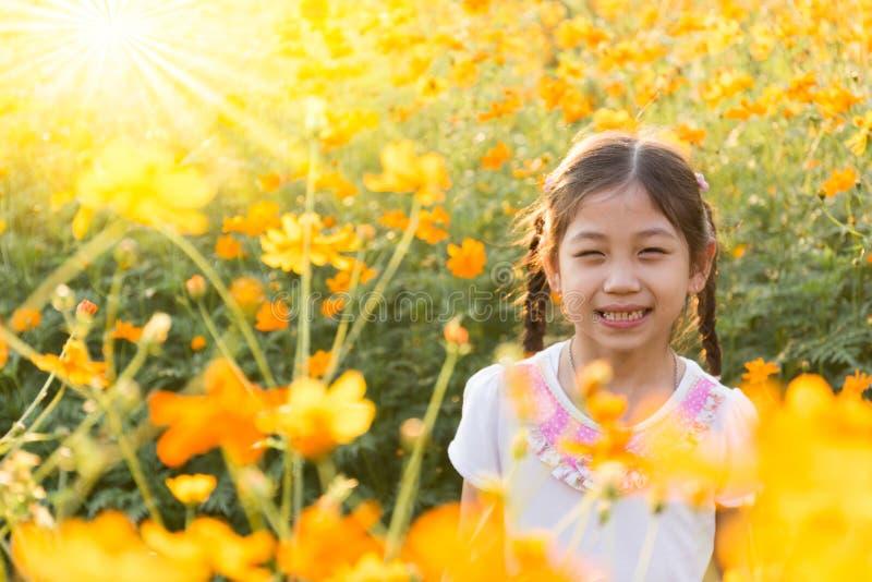 Маленькая девочка в поле желтого цвета космоса цветет на sunligh стоковое фото rf