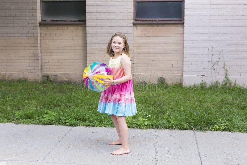 Маленькая девочка в радуге покрасила платье и босые ноги держа ясный шарик пляжа винила стоковая фотография rf