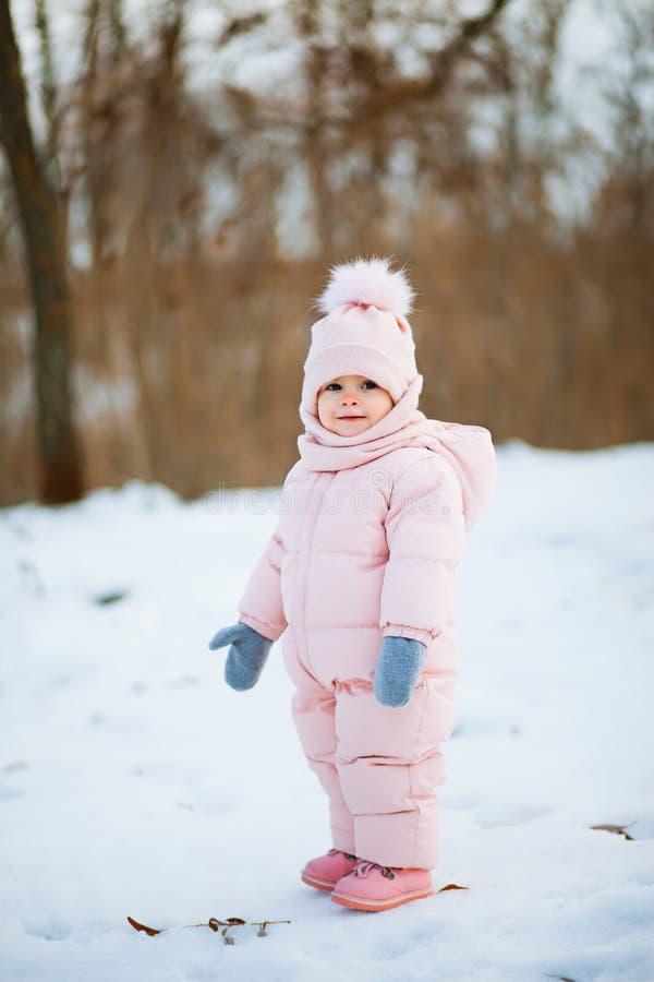 Маленькая девочка в розовом комбинезоне идет в снежный парк зимы стоковое фото rf