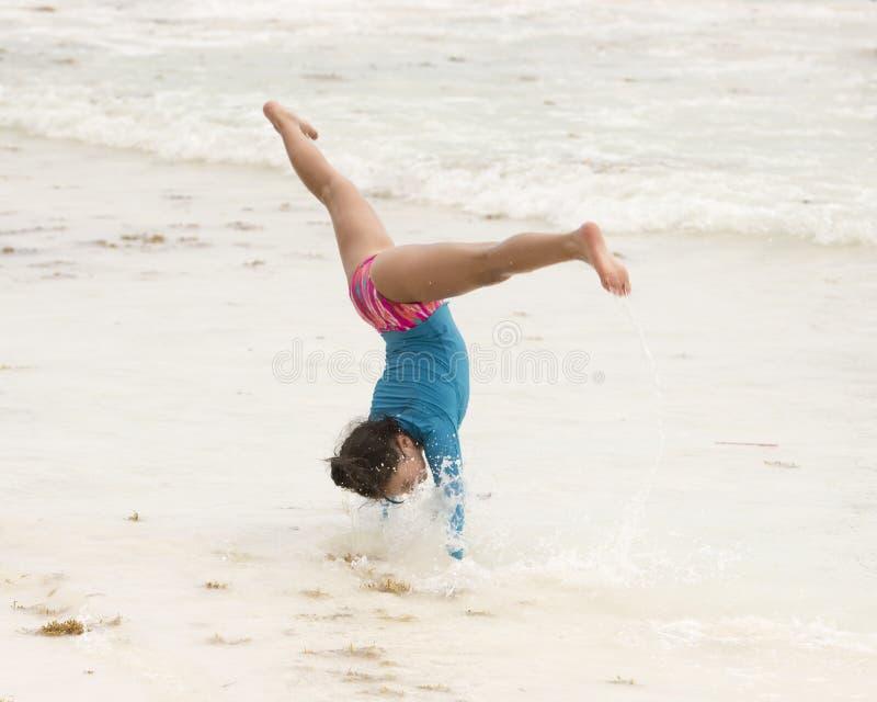 Маленькая девочка в середине колеса телеги на пляже стоковая фотография