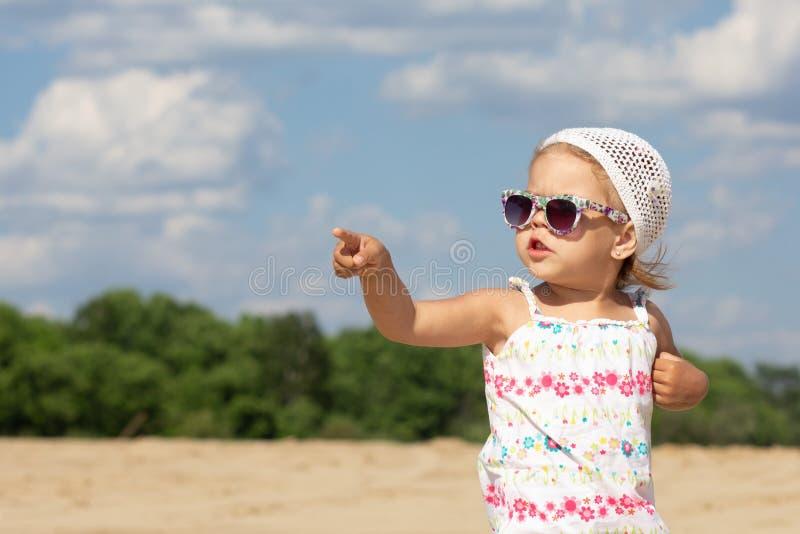 Маленькая девочка в солнечных очках указывая рука пальца в сторону и смотря в сторону стоковая фотография