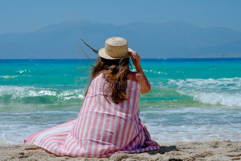 Маленькая девочка в соломенной шляпе на пляже наслаждаясь красивыми видами стоковые изображения rf