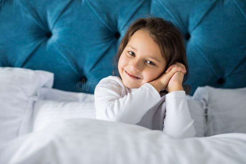 Маленькая девочка в спальне сидит на кровати Маленькая девочка носить пижамы Девушка сидя в кровати стоковая фотография