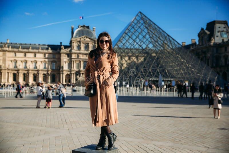 Маленькая девочка в стойках коричневого пальто и шарфа на предпосылке города Парижа Осень солнечная погода, туристы стоковая фотография rf