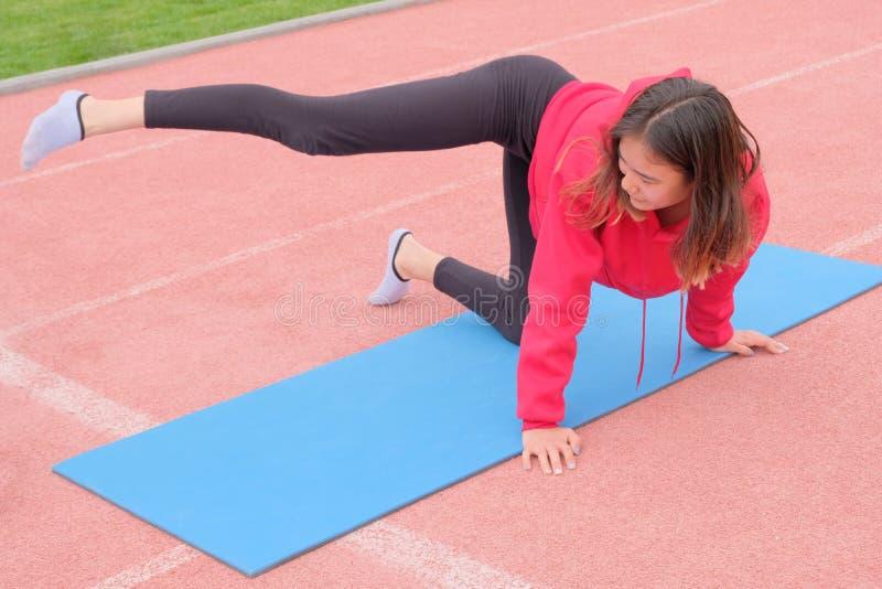 Маленькая девочка в форме спорт делая протягивать на голубой резиновой циновке на стадионе Классы фитнеса в свежем воздухе стоковые изображения rf
