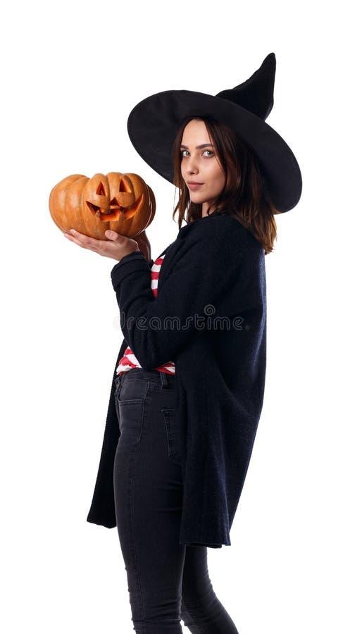 Маленькая девочка в черной шляпе, с тыквой в руках изолированных на белой предпосылке стоковая фотография