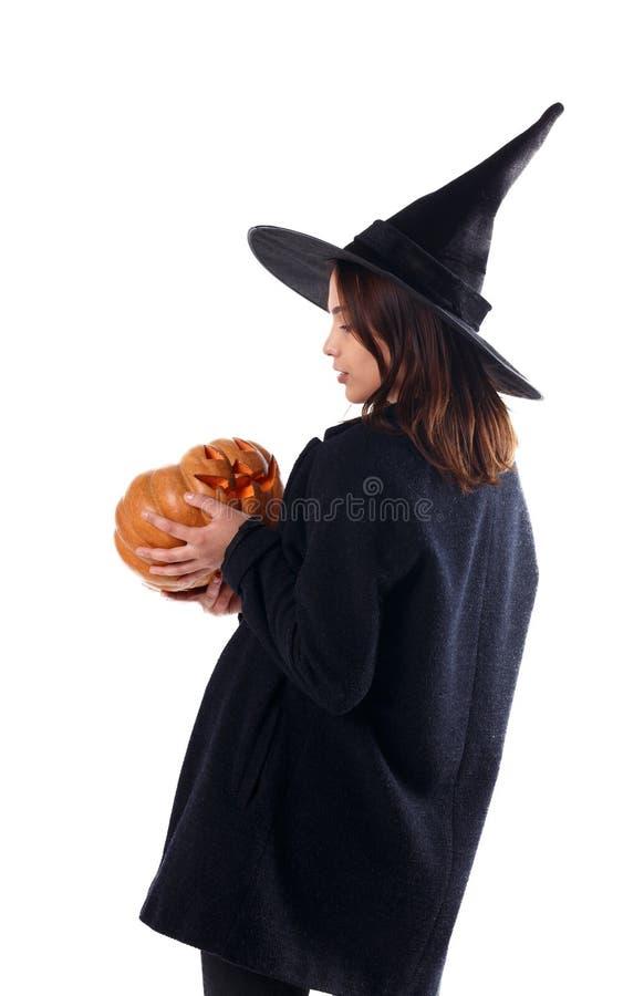 Маленькая девочка в черной шляпе, с тыквой в руках изолированных на белой предпосылке стоковое фото