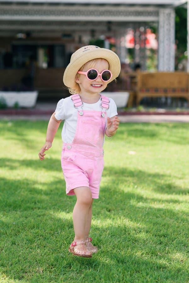 Маленькая девочка в шляпе и розовых солнечных очках имея потеху и игры на зеленой траве Беспечальная концепция детства стоковое изображение