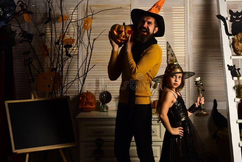 Маленькая девочка в шляпе и человеке волшебника с тыквой хеллоуина Ведьма маленькой девочки и человек волшебника празднуют хеллоу стоковое фото rf