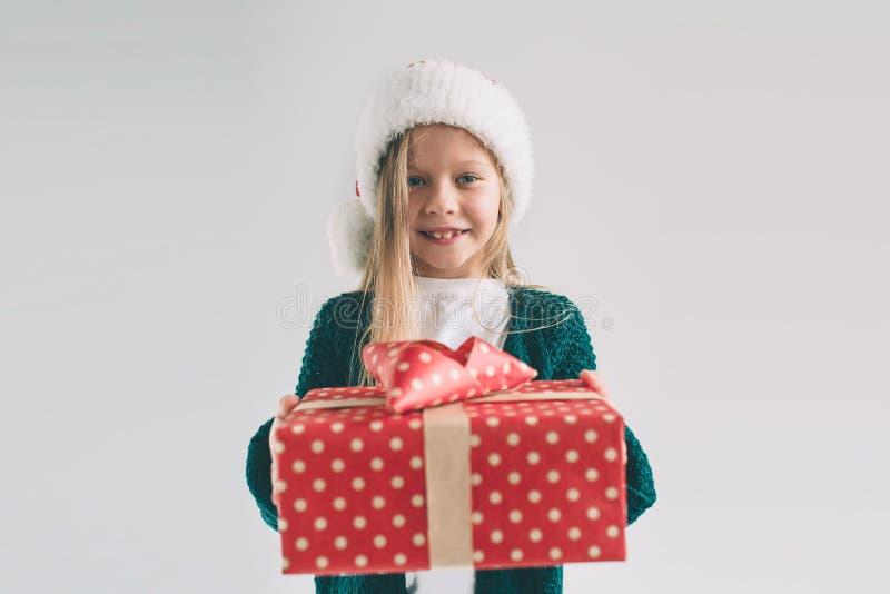 Маленькая девочка в шляпе рождества держа подарки на белой предпосылке Мы желаем вам с Рождеством Христовым и счастливый Новый Го стоковые фотографии rf
