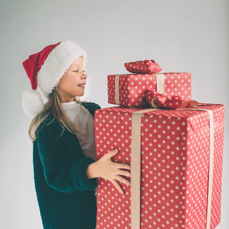 Маленькая девочка в шляпе рождества держа подарки на белой предпосылке Мы желаем вам с Рождеством Христовым и счастливый Новый Го стоковое фото rf
