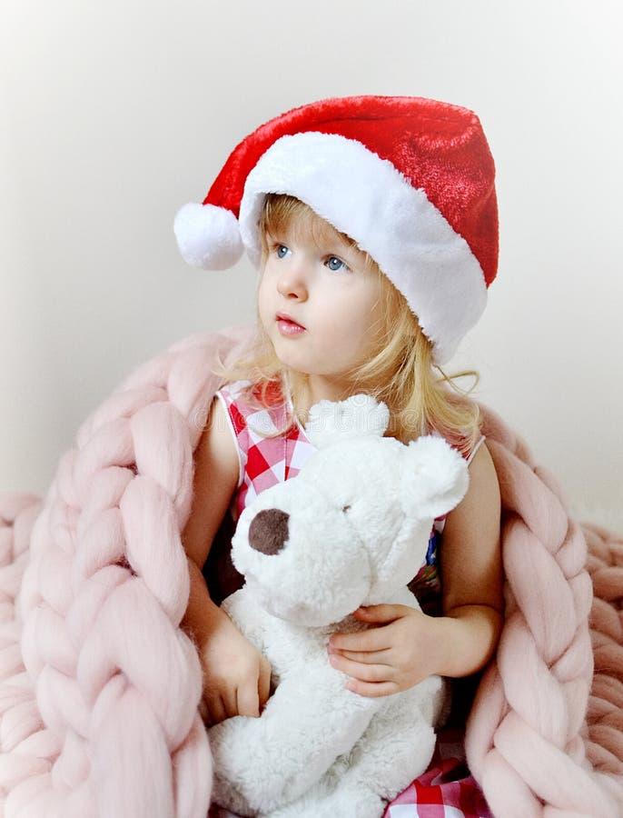 Маленькая девочка в шляпе Санты с рождеством собаки игрушки ждать стоковое изображение