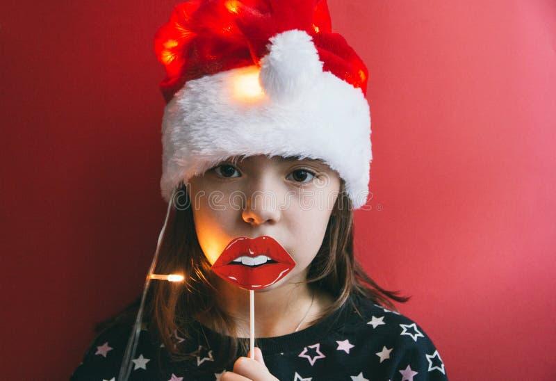 Маленькая девочка в шляпе ` s Санты красной с упорками губы на красной предпосылке стоковая фотография