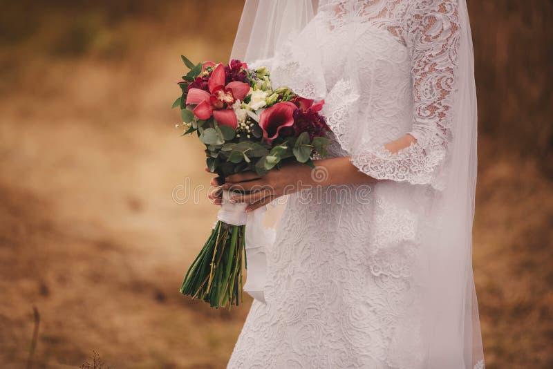 Маленькая девочка в элегантном платье стоящ и держащ букет руки пастельных цветков и зеленых цветов с лентой на природе стоковое изображение rf