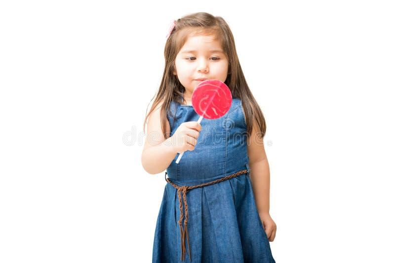 Маленькая девочка готовая для того чтобы вылизать вокруг леденца на палочке стоковые фотографии rf