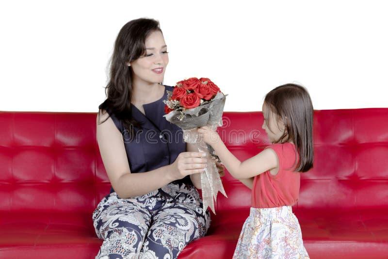 Маленькая девочка давая цветки для ее матери стоковое фото