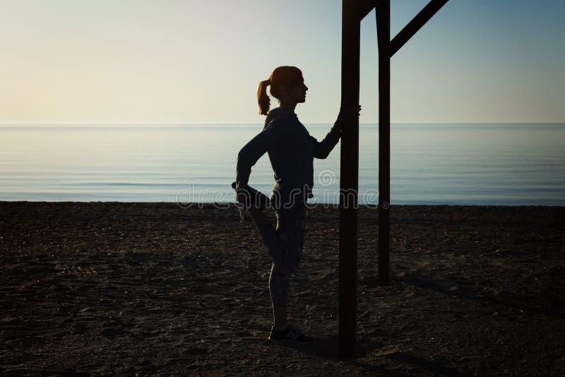 Маленькая девочка делая йогу работает на пляже моря стоковые изображения