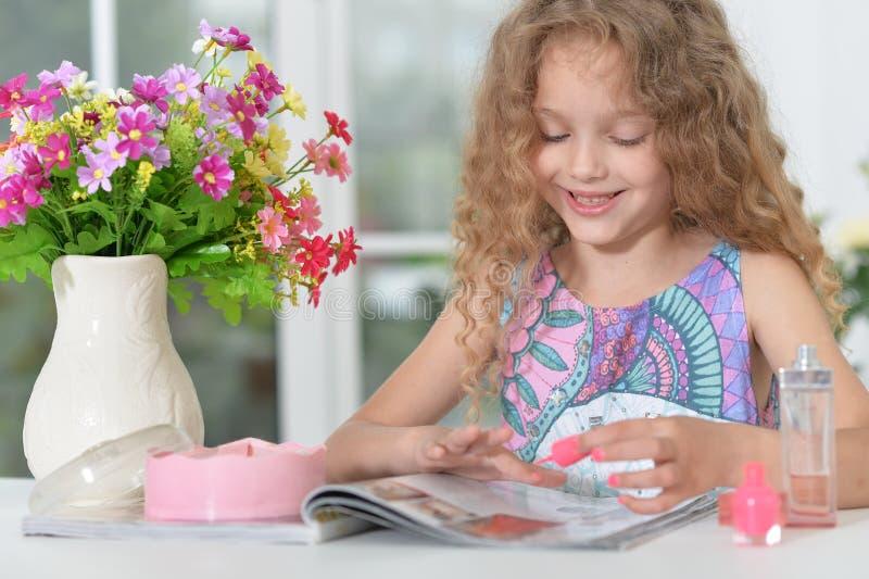 Маленькая девочка делая маникюр стоковые изображения
