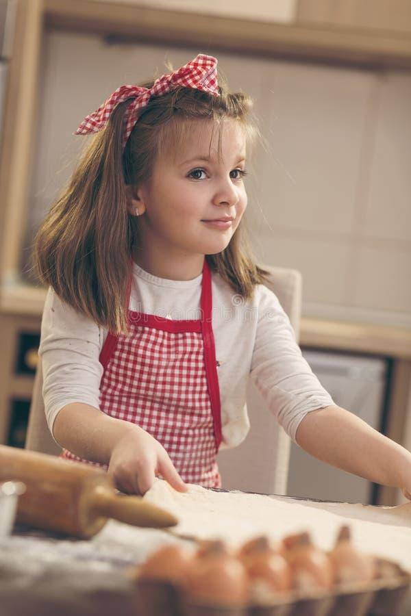 Маленькая девочка делая тесто пиццы стоковое изображение rf