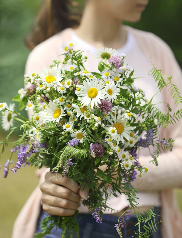 Маленькая девочка держа букет wildflowers в руках стоковое фото