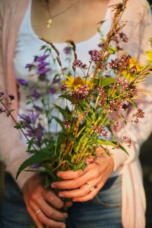 Маленькая девочка держа букет wildflowers в руках стоковые изображения