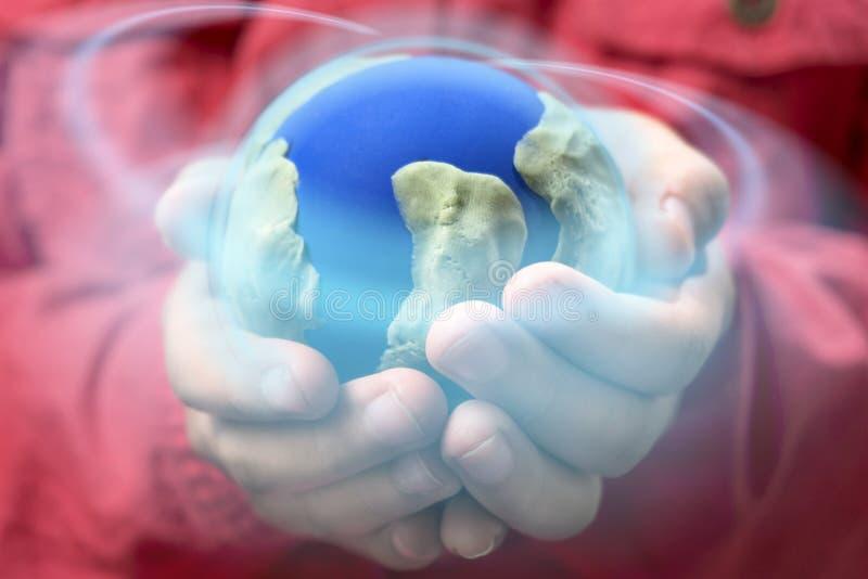 Маленькая девочка держа глобус земли с накаляя кругом на концепции глобального и окружающей среды стоковое фото rf