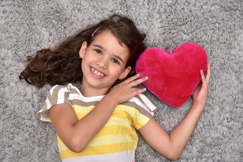 Маленькая девочка держа красное сердце плюша лежа на ковре стоковая фотография