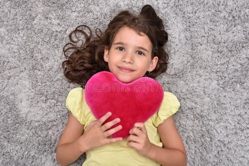 Маленькая девочка держа красное сердце плюша лежа на ковре стоковые фото