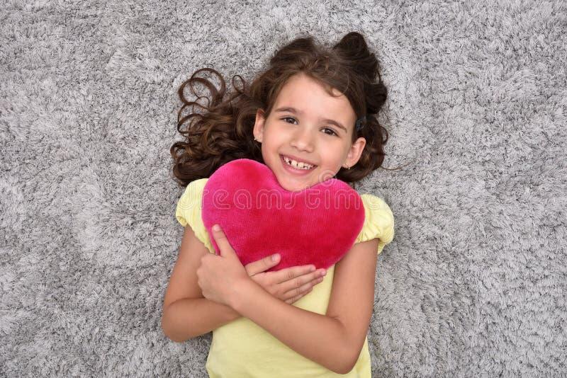 Маленькая девочка держа красное сердце плюша лежа на ковре стоковое изображение