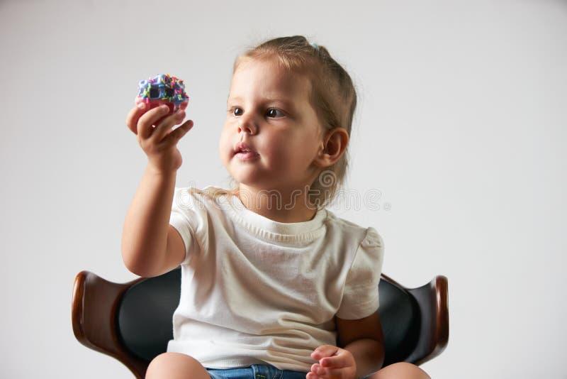 Маленькая девочка держа печенье Предпосылка изолированная белизной стоковые изображения rf