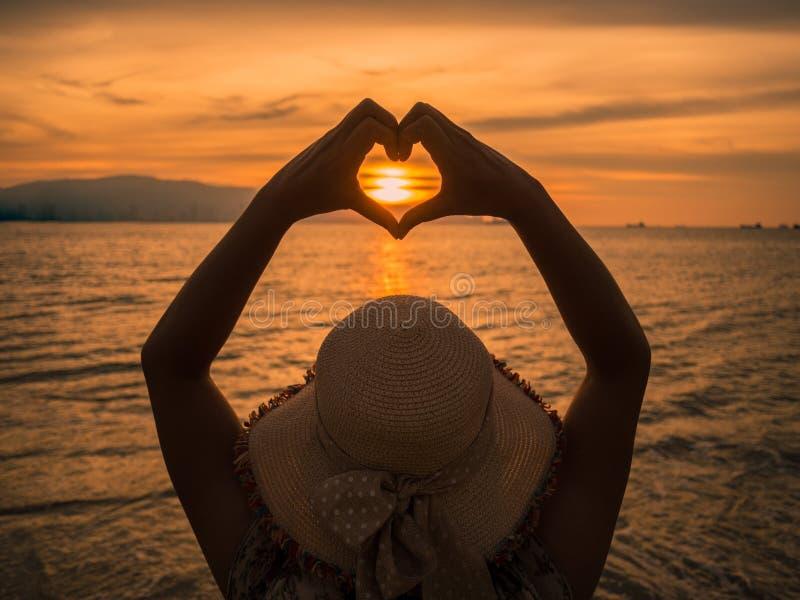 Маленькая девочка держа руки в заходящем солнце формы сердца обрамляя на заходе солнца стоковое изображение rf