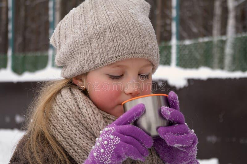 Маленькая девочка держит в ее руке крышку thermos чашки чаю outdoors на морозный день стоковые изображения